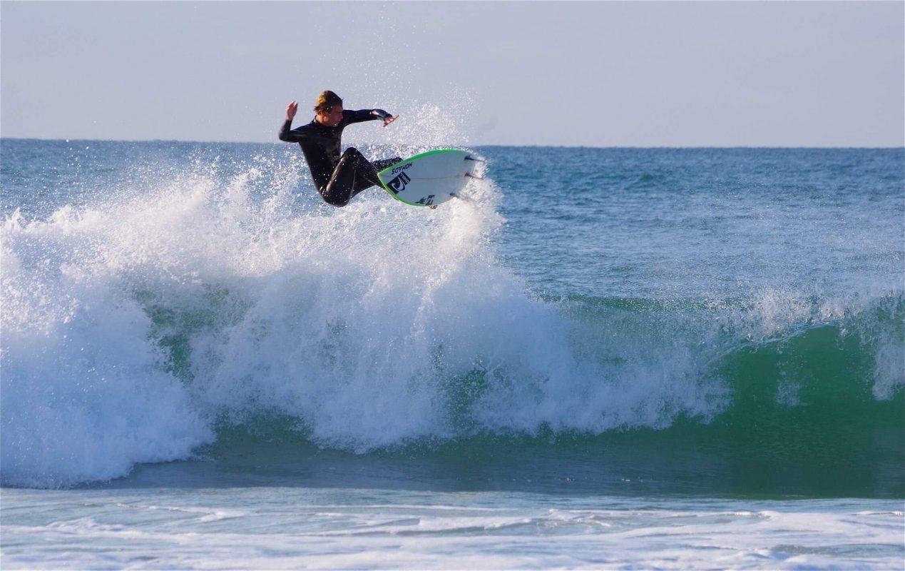 Erwan Blouin avec son surf au dessus de la vague 1269x800 - Rencontre avec Erwan Blouin un surfeur engagé