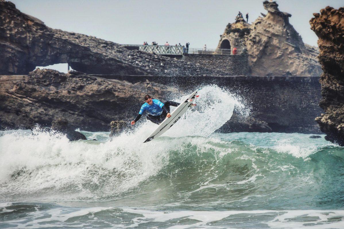 Erwan Blouin avec son surf en haut de la vague 1198x800 - Rencontre avec Erwan Blouin un surfeur engagé