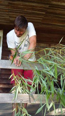 Pierre qui scie du bambou pour faire une paille bio