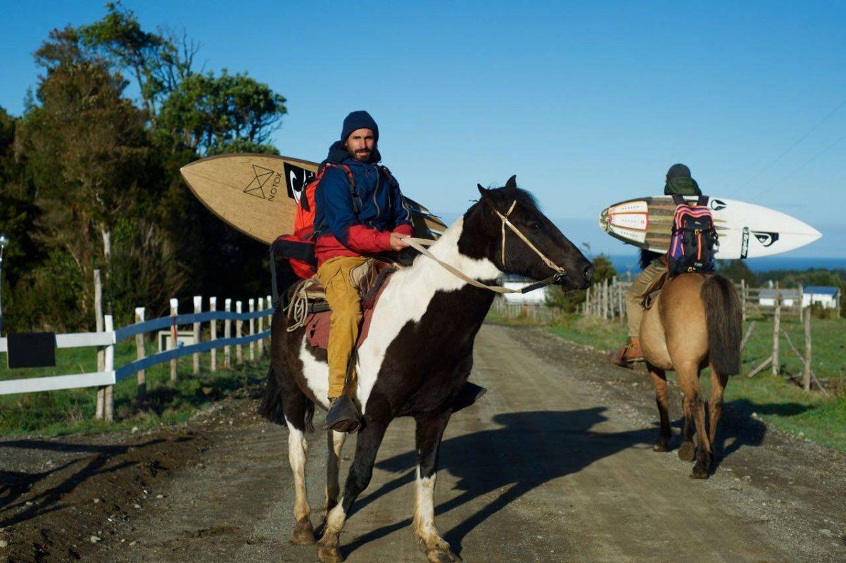 Damien Castera en cheval avec son surf sur le dos
