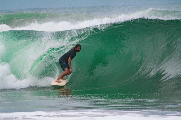 Damien Castera en surf dans un rouleau