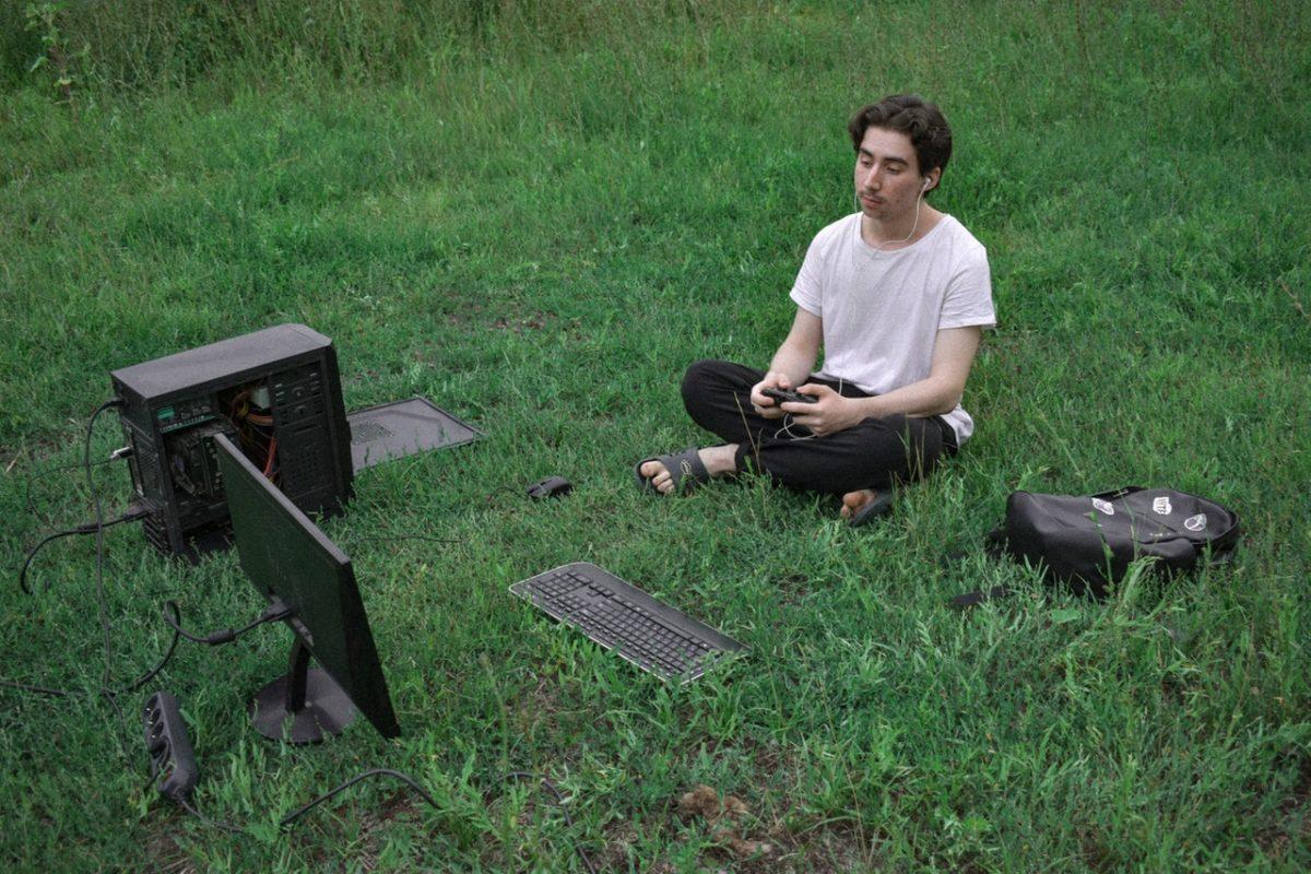 homme assis dans l'herbe face à un ordinateur