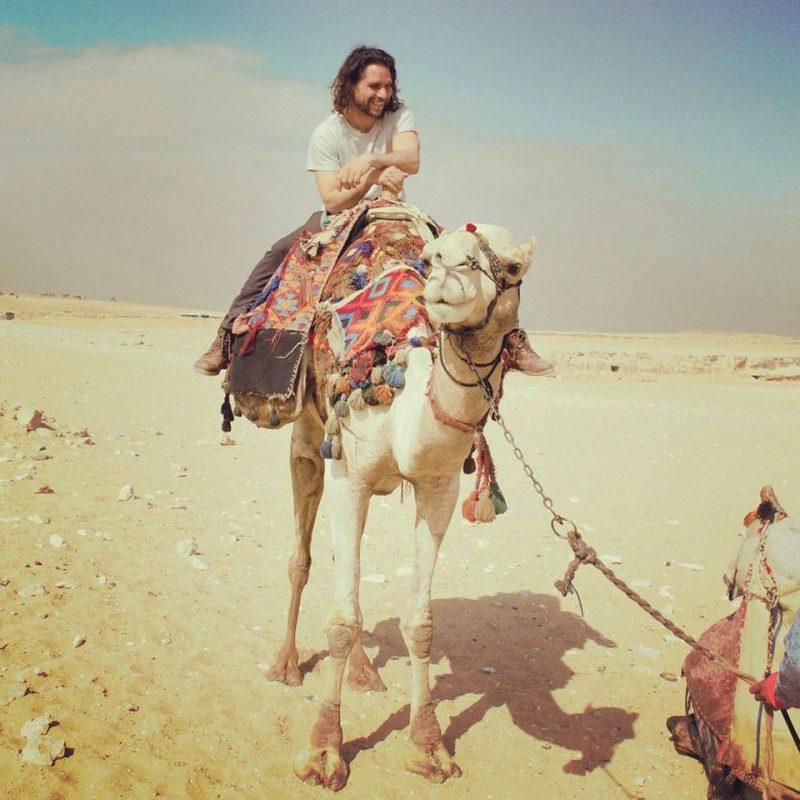 Erwan sur le dos d'un chameau dans le désert