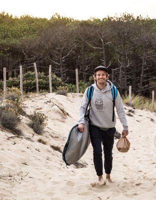 Nicolas marche sur le sable avec sa planche de surf sous le bras