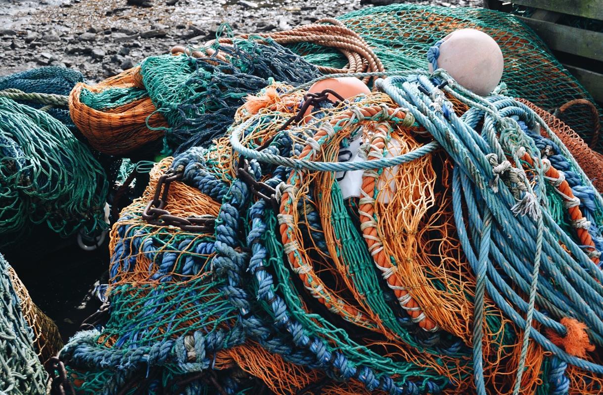 filets de pêche de toutes les couleurs entassés sur le quai d'un port